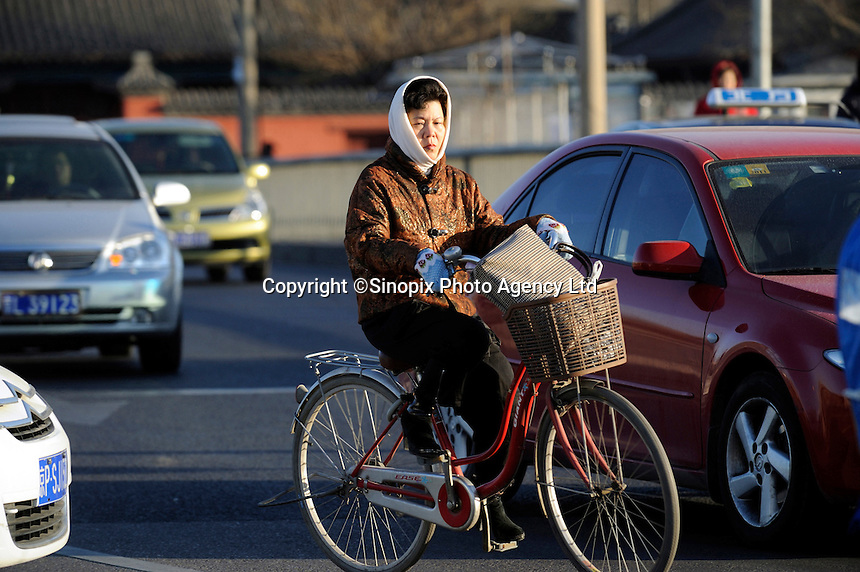 A lady rides a bicycle on roads packed with cars in Beijing, China. China used to be known as the 'kingdom of bicycles', but currently, more and more people gave up commuting by bike for security and health. The number of car owners in the city climbed from 2 million in 2003 to more than 4.76 millon, according to the Beijing Municipal Commission of Transport..09 Mar 2011