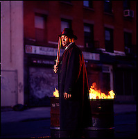 Man with night stick standing next to flaming trashcans<br />