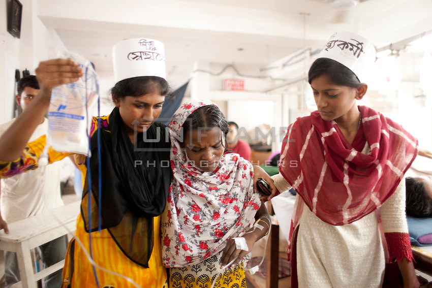 Volunteers help a garments worker to walk during the hunger strike. Workers of Tuba garments are now suffering from the consequences of the hunger. They are being helped with  intravenous saline drips inside the garments factory. Dhaka, Bangladesh
