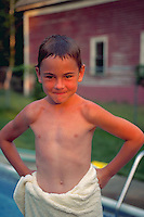Portrait of smiling boy standing with a towel around his waist by a pool.