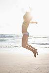USA, Florida, St. Pete Beach, Girl (8-9) in bikini jumping on beach