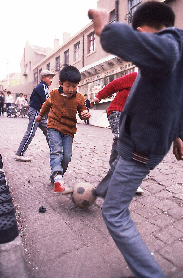 Children played soccer until an errant ball ended up on top of a low shop roof and the proprietors chased the player away without retrieving the ball. Photographs by Jim Mendenhall shot for the 1989 Day in the Life of China book. His assignment was to cover a major industrial city, Tsing Tao. One of his few assignments was to shoot the Tsing Tao brewery but the workers were on holiday the day the book was shot. What turned out to be his primary assignment was a murder trial.