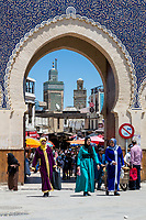 Fes, Morocco.  Bab Boujeloud, Women in Colorful Djellabas and Headscarfs Exiting Fes El-Bali, the Old City.  The minaret of the Bou Inania medersa is in the background.