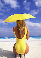 Young woman in yellow swimsuit with yellow parasol on beach