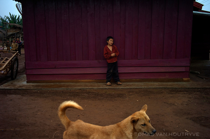 A boy and a dog stand near a home in the ethnic Hmong village of Ban Tachok, Xieng Khoung province, Laos on March 18, 2011.