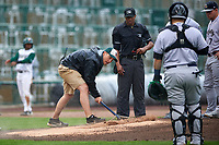 Field crew members repair the mound as the rain begins to fall during a Midwest League game between the Kane County Cougars and Fort Wayne TinCaps at Parkview Field on May 1, 2019 in Fort Wayne, Indiana. Fort Wayne defeated Kane County 10-4. (Zachary Lucy/Four Seam Images)