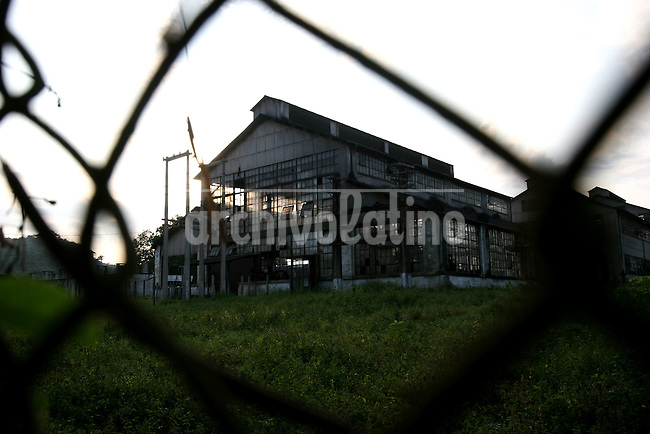 A factory building is seen through a fence in Fordlandia, a former factory town created by the Ford Motor Company on the banks of the Tapajós River, September 6, 2005. Deep in the Amazon forest, 12 hours by boat from the regional capital of Santarem in Brazil's Pará state, the rubber plantation and processing factory is now abandoned to the rain-forest, an aging memorial to American ideals and to the Brazilian reality. It almost seems like time has stopped in Fordlandia, or better yet, time has passed it by. In typical american style, it was organized and efficient, an idea admired by many Brazilians, and perhaps more so by residents of the untamed Amazon. But It is an idea hard to implement in the wilds of the amazon. Some might also say that it is also a typical American style the way Ford came here and tried to implement something with little knowledge of the local customs or terrain. From 1928 to 1945, Ford came tried to take control of his rubber supply, one of the most important products of the rainforest. After only 17 years the company admitted defeat and retreated from the forest.