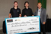 IMSA COO and President Scott Atherton presents a scholarship check for $100,000 to Austin McCusker and Rodrigo Pflucker