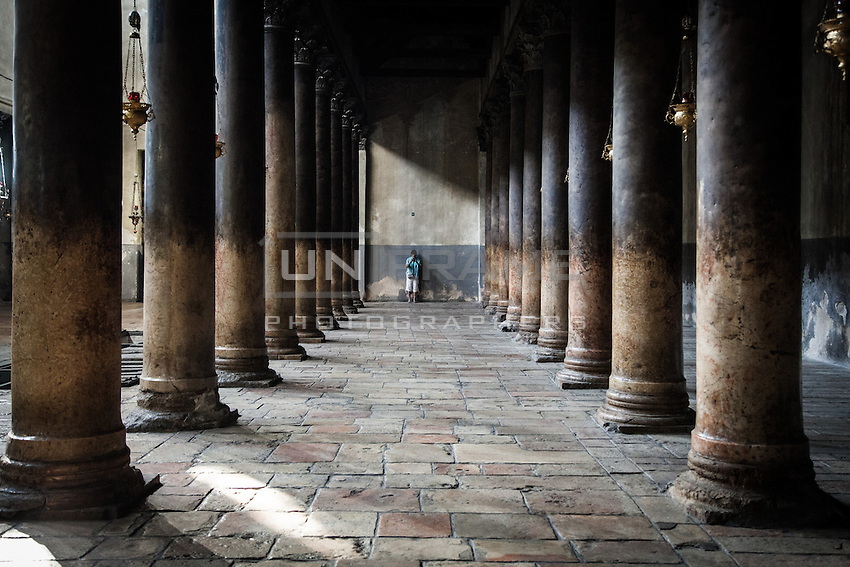 A pilgrim in the left nave of the Bethlehem's Church of Nativity