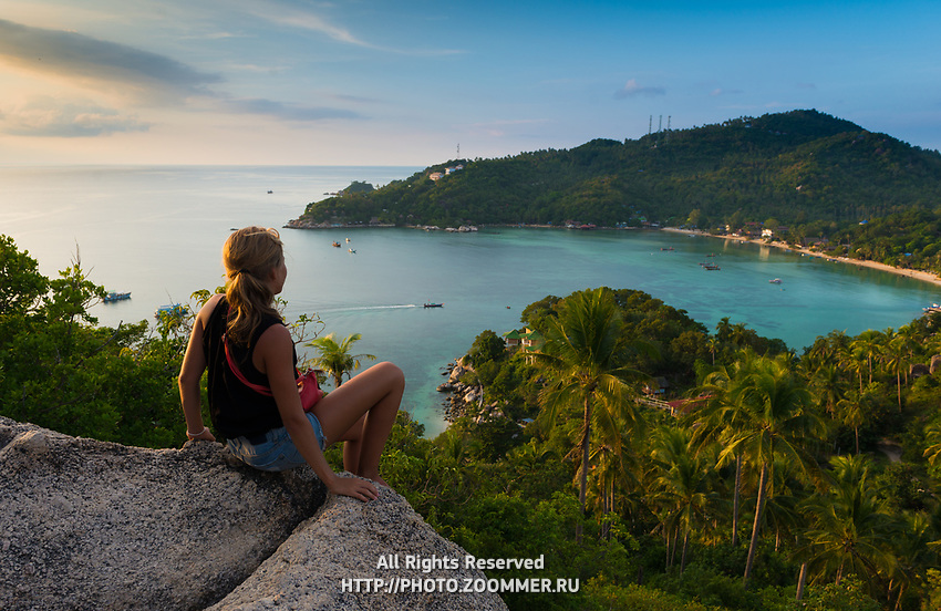 Girl sitting on a rock with panoramic view of Ko Tao island, Thailand