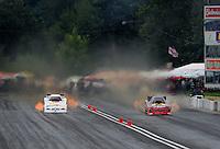 Aug. 6, 2011; Kent, WA, USA; NHRA funny car driver Melanie Troxel (right) races alongside Brian Thiel during qualifying for the Northwest Nationals at Pacific Raceways. Mandatory Credit: Mark J. Rebilas-