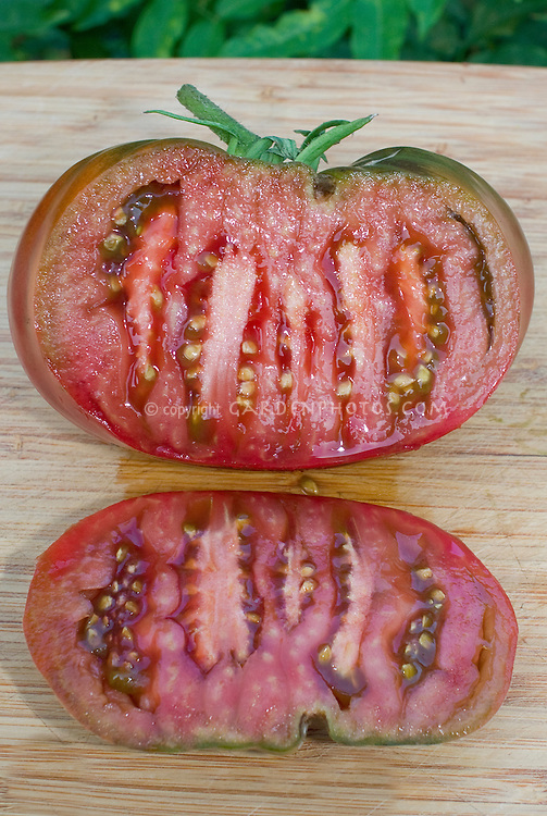 Tomato Black Krim picked and sliced open to show interior inside of vegetable fruit with seeds, heritage antique variety of beefsteak tomatoes