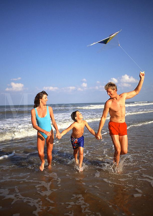 Family flying a kite on beach