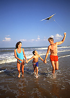 Family flying a kite on beach