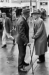 Senior men with walking sticks and wearing hats, chat in the rain. Market Day, Holsworthy Devon. 1970s England 1975