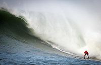 Half Moon Bay, California - January 24, 2014: 2014 Maverick's Invitational Shane Dorian making it safely to the bottom.