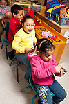 Education Preschool 4-5 group of girls and boy playing driving bus game in line of chairs