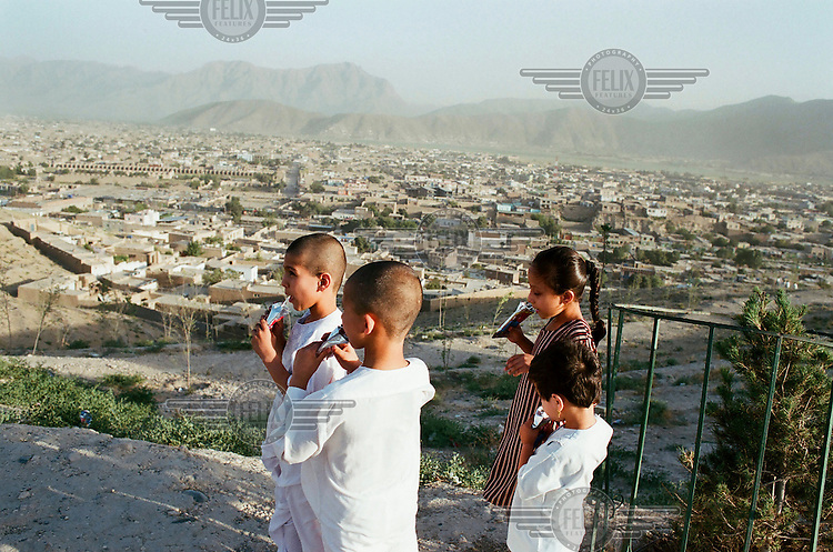 Children drinking soft drinks on Tapa Marajan Hill, the site of the Mausoleum of the ancient King Nadir Shah..