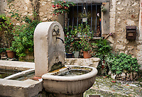 A rustic water fountain in a courtyard in the village of St Paul de Vance, Provance, France