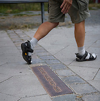 A man steps across a plaque marking where the Berlin Wall used to be.