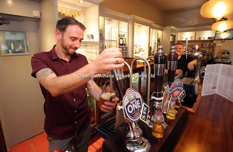 Gwilym John serves a pint of lager at the bar