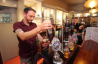 Gwilym John serves a pint of lager at the bar