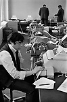 1970s office work City of London. Ticker tape machines, used for transmitting stock price information over telegraph lines, in use from around 1870 through 1970.