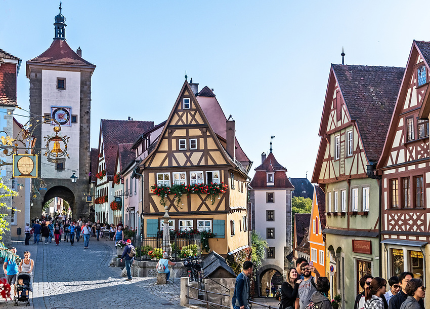 """This is the Plönlein, or """"Little Plaza,"""" of Rothenburg, probably the most popular tourist spot in the town. It includes, in addition to a small fountain and several half-timbered buildings, two medieval towers, both completed in the year 1204. The higher tower, on the left, is the Siebers Tower, and the lower one to the right is the Kobolzeller Tower. They are part of the inner circle of medieval fortifications of the town. — in Rothenburg ob der Tauber."""