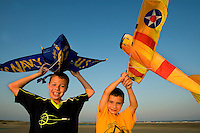 Two boys pose for a picture at sunset with their kites.