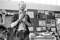 """Photographer, John Walmsley shooting the visit by American educationalist, John Holt to Julian's Primary School, Streatham, London.  1971.  John Walmsley is the author of """"Neill & Summerhill: a man and his work"""" about A.S.Neill and the democratic school he founded, Summerhill, published by Penguins in 1969.  He went on to photograph education in the UK over the next 40+ years."""