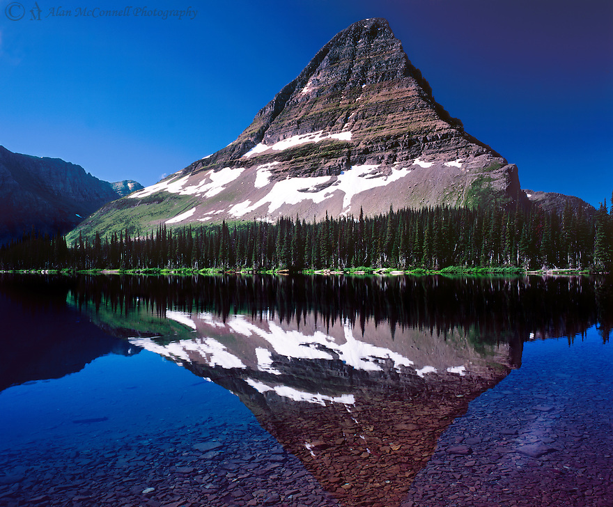 Morning light reflects off Bearhat Mountain onto Hidden Lake.  This 5.3-mile round trip hike starts at the Logan Pass Visitor Center.  After ascending 1.4 miles, one will reach the Hidden Lake Overlook, where most people turn back.  At this point, the trail continues for another 1.3 miles, descending 747', and at times a -60% grade.  Your reward after reaching the cold clear waters of Hidden Lake is a wonderful solitude from the typically large mass of tourist.