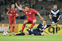 MELBOURNE, AUSTRALIA - OCTOBER 30: Paul Reid of United and Adrian Leijer of the Victory compete for the ball during the round 12 A-League match between the Melbourne Victory and Adelaide United at Etihad Stadium on October 30, 2010 in Melbourne, Australia.  (Photo by Sydney Low / Asterisk Images)