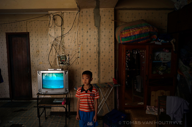 A boy stands near a television in his home inside an apartment building constructed by Soviet architects in 1985 in Vientiane, Laos on March 27, 2011.