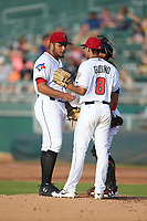 Lansing Lugnuts third baseman Yeltsin Gudino (8) chats with starting pitcher Maximo Castillo (25) and catcher Andres Sotillo (16) on the mound during the game against the South Bend Cubs at Cooley Law School Stadium on June 15, 2018 in Lansing, Michigan. The Lugnuts defeated the Cubs 6-4.  (Brian Westerholt/Four Seam Images)