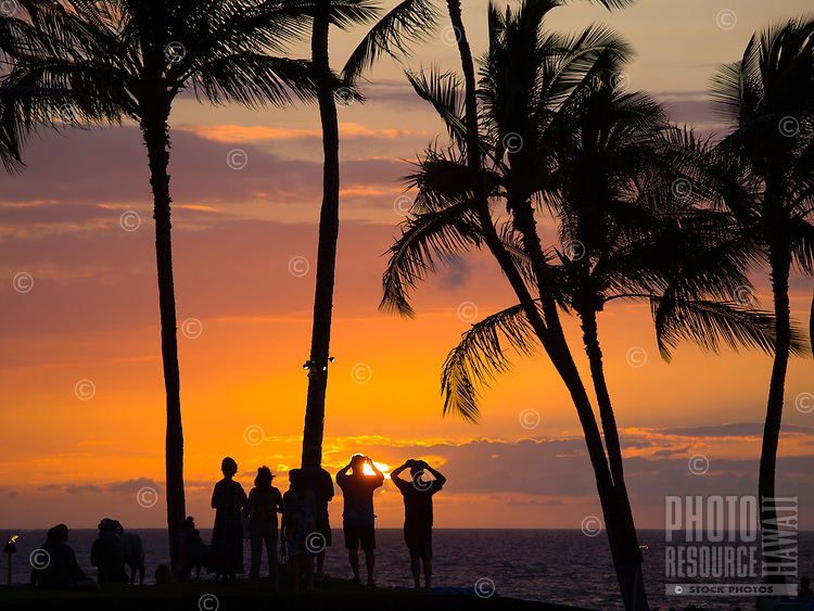 People silhouetted against a beautiful sunset take pictures of it in Waikoloa, Big Island.