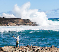 A fisherman fixes his bait while powerful waves pound the distant shoreline at La'ie Point, North Shore, O'ahu.