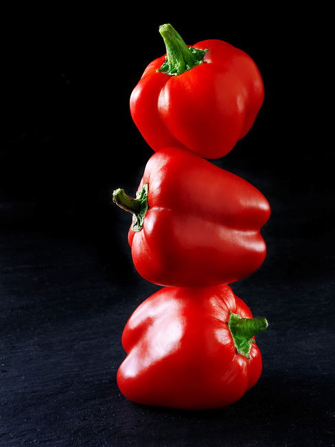 3 red peppers balanced on top of each other against a black background