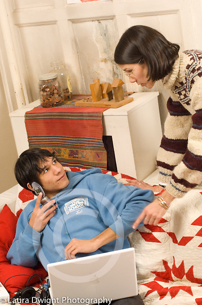 Teenage boy 16 years old sitting on couch with laptop computer and cell phone argument or discussion with mother