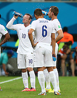 Wayne Rooney of England squirts water on to his face to cool down from the hot conditions in Manaus
