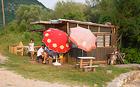 A ramshackle road side roadside bar with sun shade umbrellas. Two men sitting drinking wine and a young girl. Near Dupilo, Golubovic Montenegro, Balkan, Europe.
