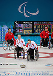Sochi, RUSSIA - Mar 10 2014 -  Mark Ideson takes a shot as Dennis Thiessen looks on during Canada vs USA in Wheelchair Curling round robin play at the 2014 Paralympic Winter Games in Sochi, Russia.  (Photo: Matthew Murnaghan/Canadian Paralympic Committee)