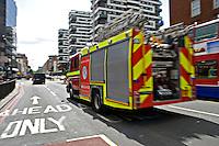 London Fire Brigade Fire engine on emergency call driving through traffic, London, UK..
