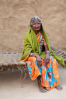 Bharatpur, Rajasthan, India.  Old Woman Sitting on a String Bed in Front of her House.  She wears a dupatta (scarf) over her head and shoulders.