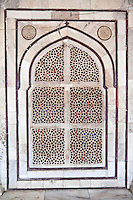 Fatehpur Sikri, Uttar Pradesh, India.  Inside the Mausoleum of Sheikh Salim Chishti.  Geometric Design in Laticework Window.  Red or yellow strings tied to the window are left by visitors praying  for Sheikh Salim's assistance, usually in conceiving a child.