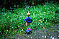 Child age 4 responding to the call of nature along forest trail