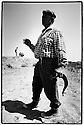 Uzbekistan - Aral Sea - A fisherman holding a fish in his hand.