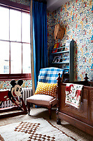 A child's bedroom has walls covered in 'Alice in Wonderland' wallpaper, a 30's design by CFA Voysey