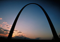 The famous St. Louis Arch is visible while illuminated by soft, blue and orange sunset light. St. Louis Missouri.