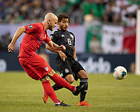 CHICAGO, IL - JULY 7: Michael Bradley #4 is defended by Jonathan Dos Santos #6 during a game between Mexico and USMNT at Soldier Field on July 7, 2019 in Chicago, Illinois.