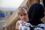 DOMIZ, IRAQ: A mother holds her child in the Domiz refugee camp..Over 7,000 Syrian Kurds have fled the violence in Syria and are living in the Domiz refugee camp in the semi-autonomous region of Iraqi Kurdistan...Photo by Ali Arkady/Metrography